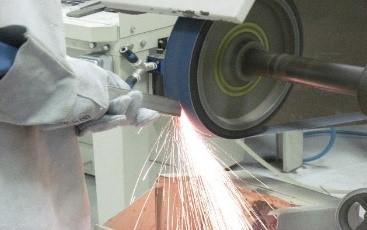 Operator szlifuje metalowy element za pomocą taśm ściernych bluefire